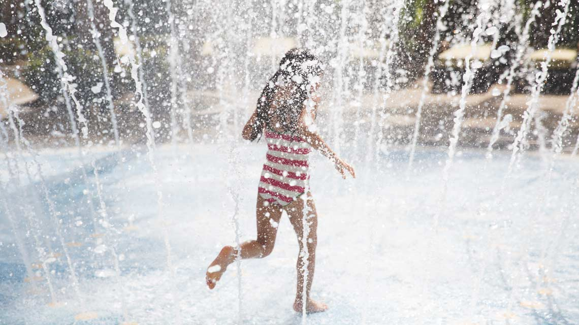 Girl at outdoor pool running through sprinklers