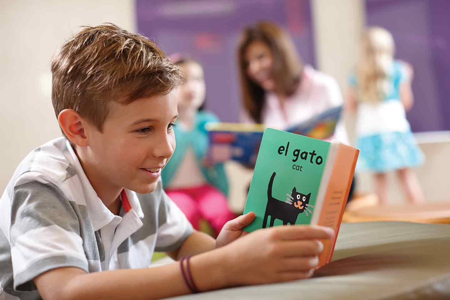 A boy reading a book during Life Time afterschool care