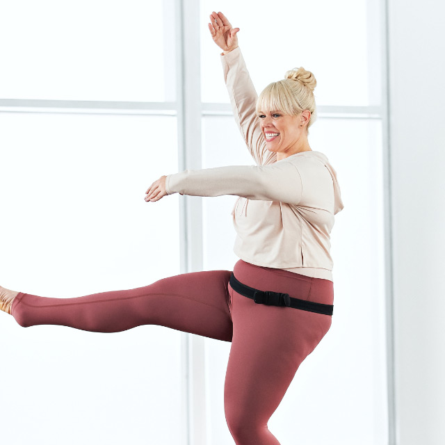 Woman taking a Family Barre class at home with Life Time Classes On Demand