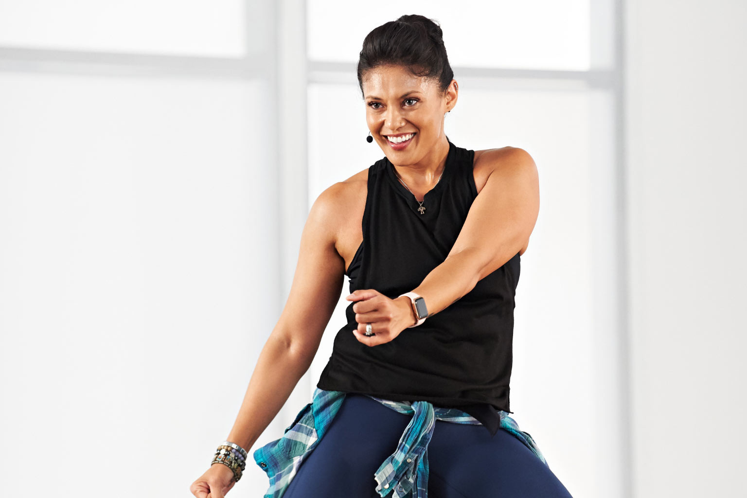 Woman taking a Zumba class at home with Life Time Classes On Demand.