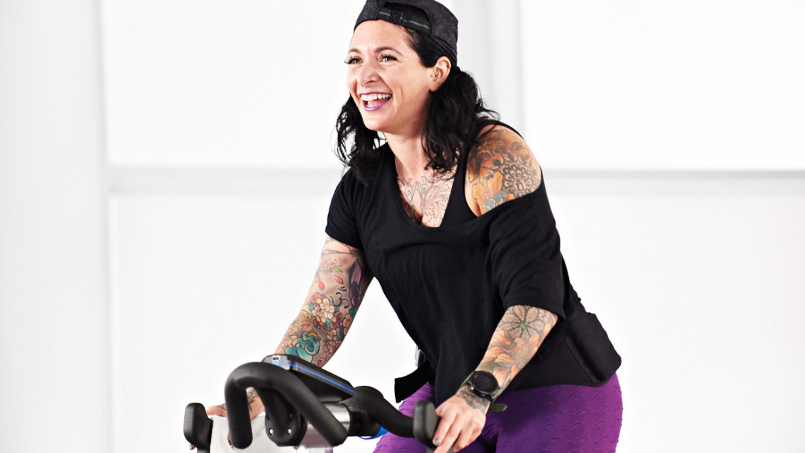 Woman taking a PWR cycle class at home with Life Time Classes On Demand.
