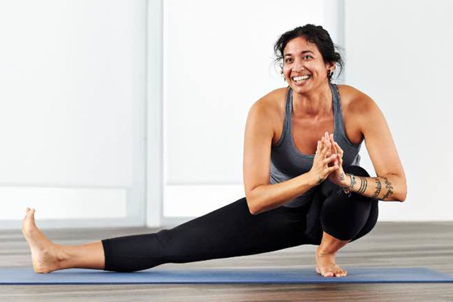 Woman taking a Surrender yoga class at home with Life Time Classes On Demand.