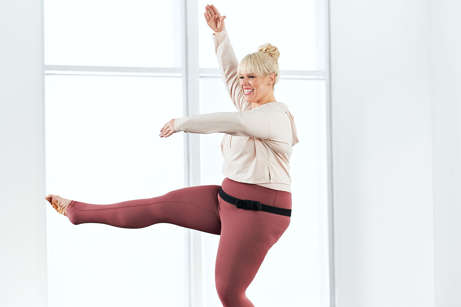 Woman taking a Family Barre class at home with Life Time Classes On Demand.