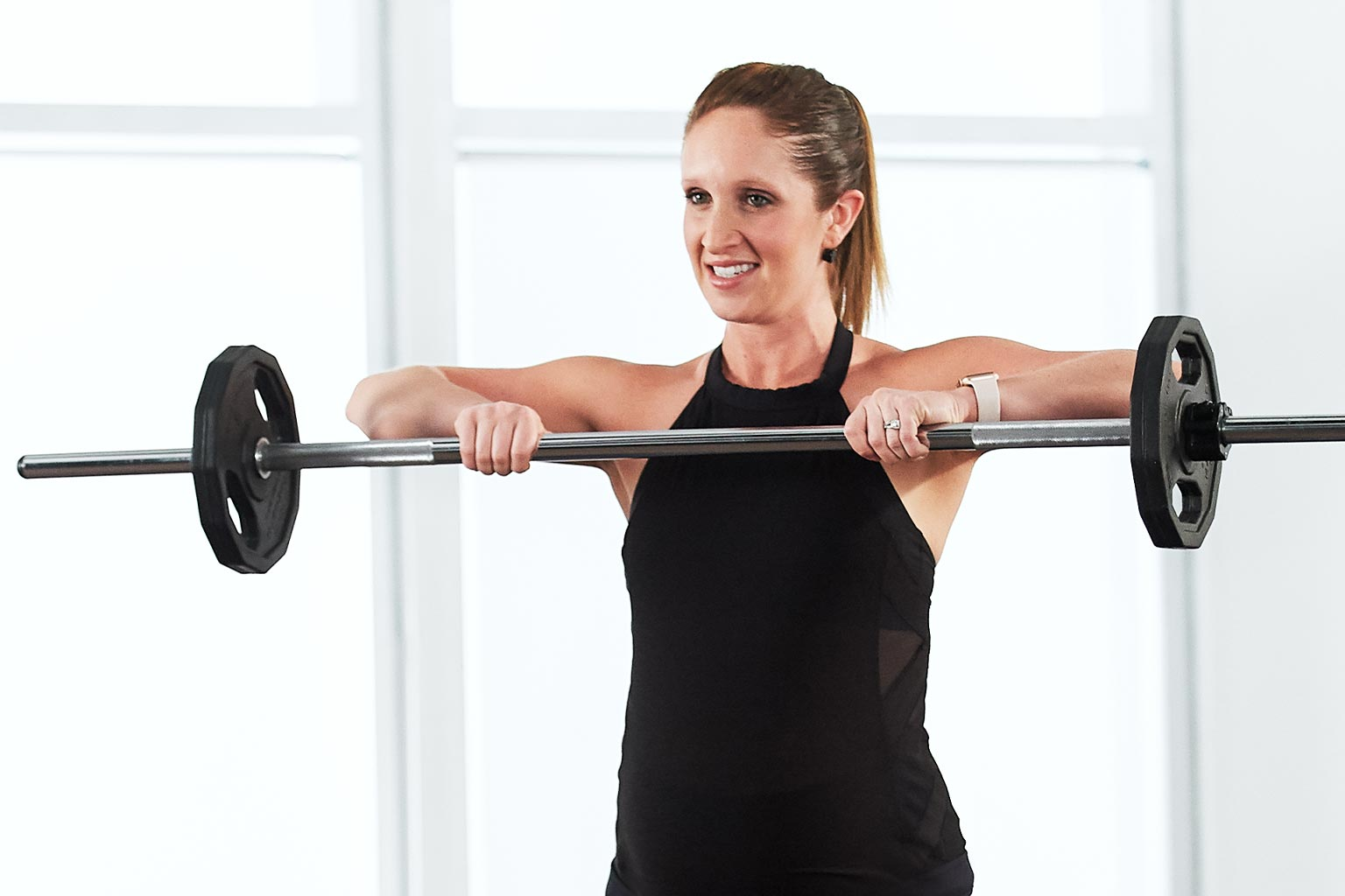 Woman taking a Barbell Strength class at home with Life Time Classes On Demand.