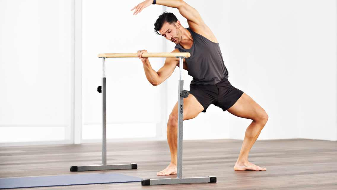 a man taking an En Barre class at home with Life Time Classes On Demand