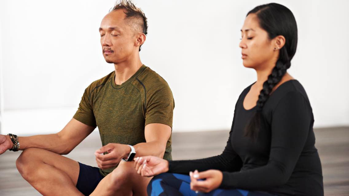 A man and woman taking a guided meditation class at home with Life Time Classes On Demand