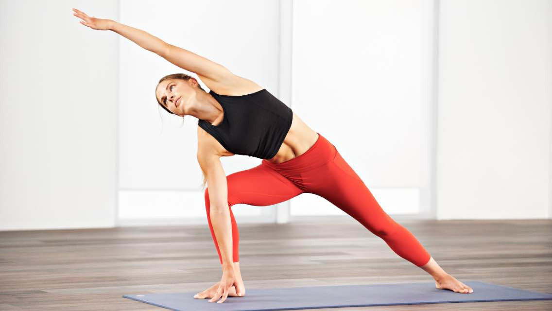 Woman taking a yoga SOL class at home with Life Time Classes On Demand