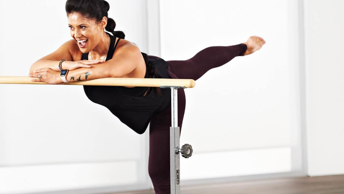 A woman taking an En Barre class at home with Life Time Classes On Demand