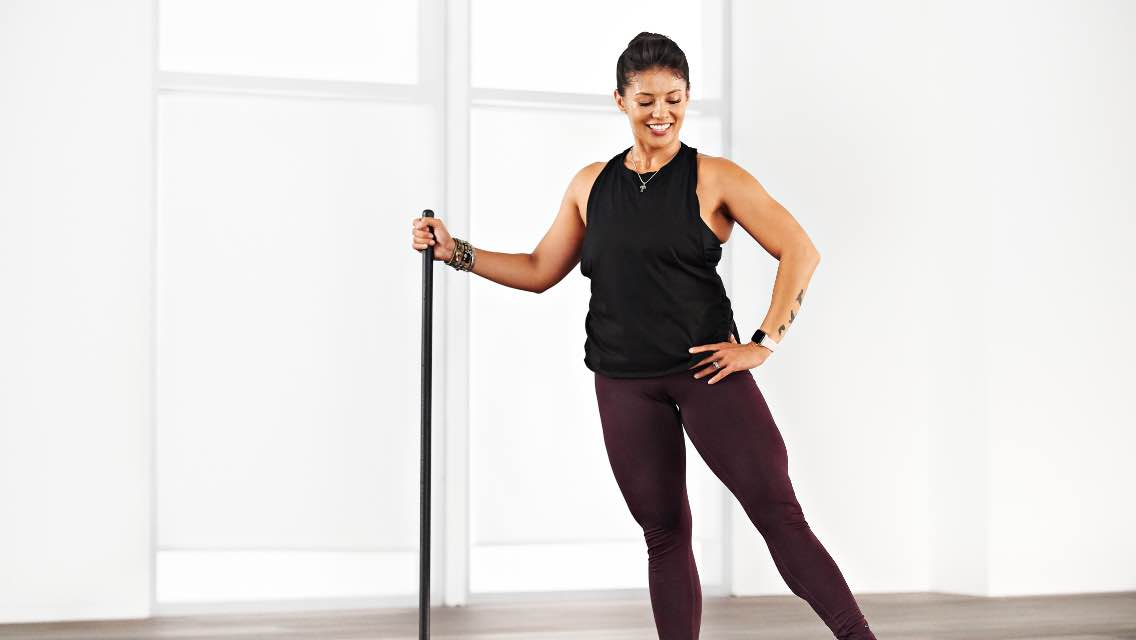 A woman doing an at home Life Barre workout with Life Time Classes on demand