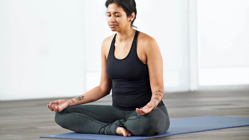 Woman taking a Guided Meditation class at home with Life Time Classes On Demand