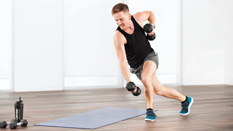 A man holding weights while doing lunges at home with Life Time Classes On Demand