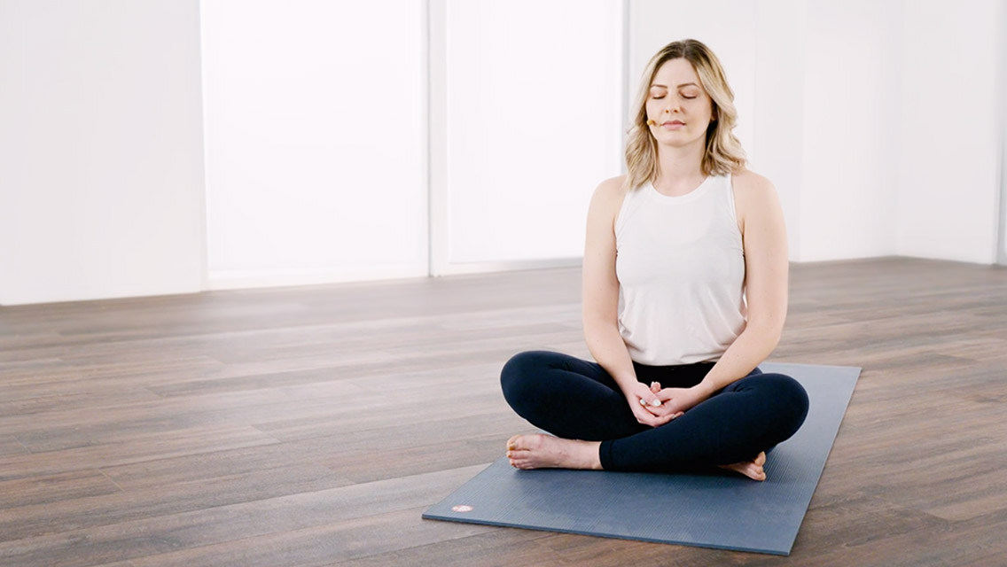 Woman sitting on a yoga mat meditating