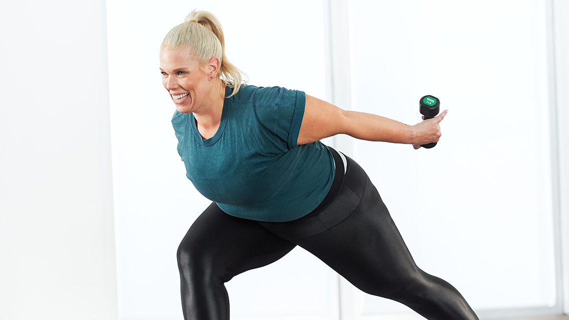 a woman in a bent over lunge with dumbbells in her hands