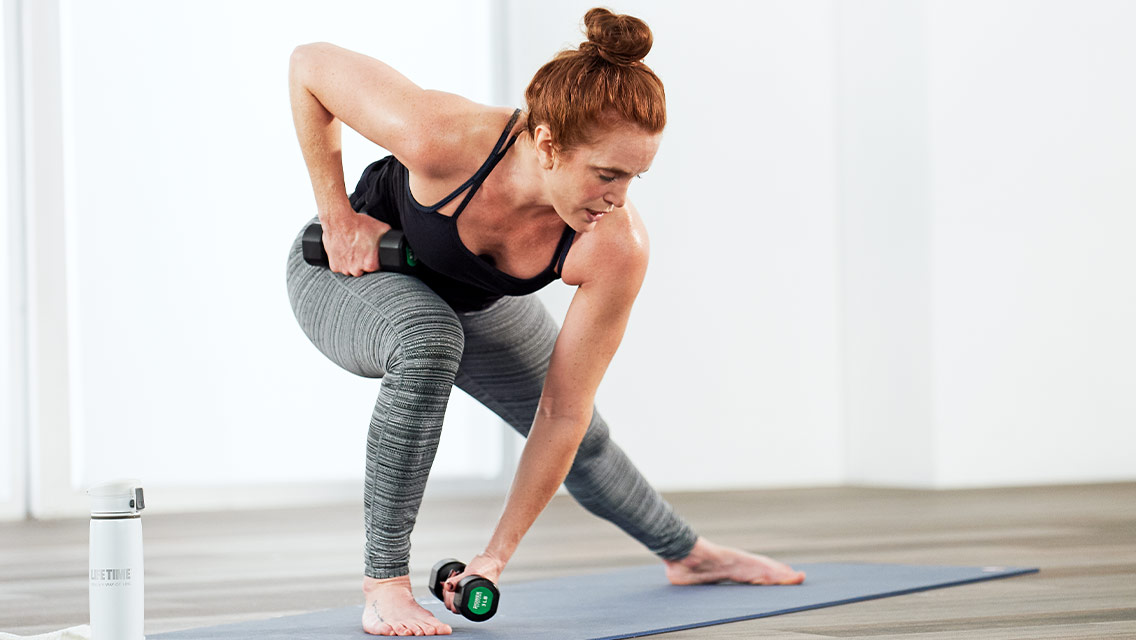 Woman lunging to the side with a dumbbell