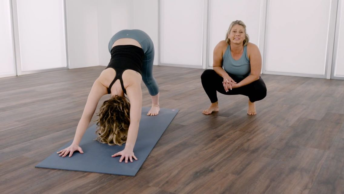 Woman holding a downward dog position on a yoga mat