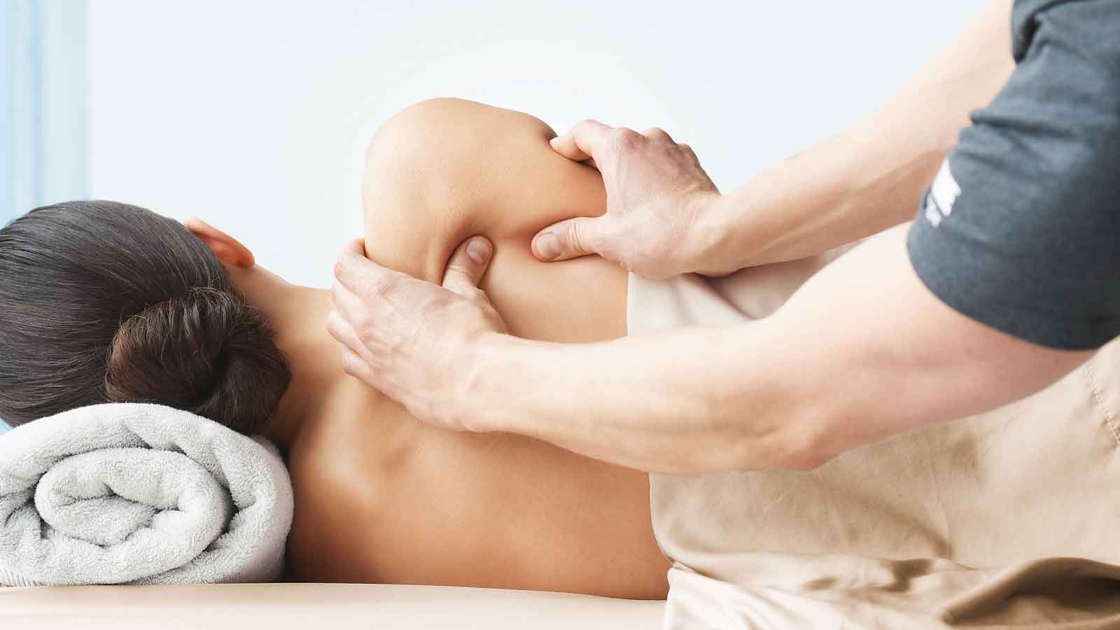 A massues pressing into the shoulders of a women laying on her side on a massage table