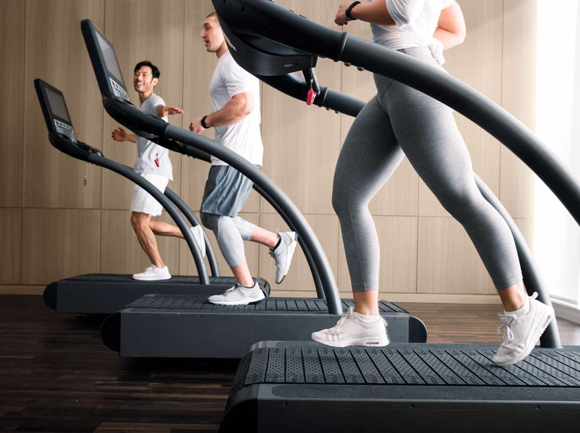 A woman and two men jog on side-by-side treadmills.
