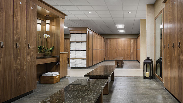 View of Life Time's luxurious locker rooms, wood lockers, marble benches, and towels.