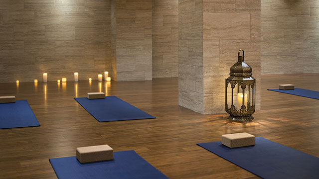 A yoga studio, with candles, lanterns, yoga mats and yoga blocks laid out.