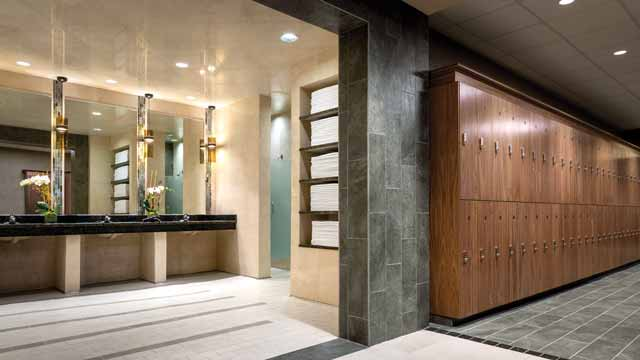 A counter and sinks in a spa-inspired locker room, providing complimentary toiletries and hairdryers