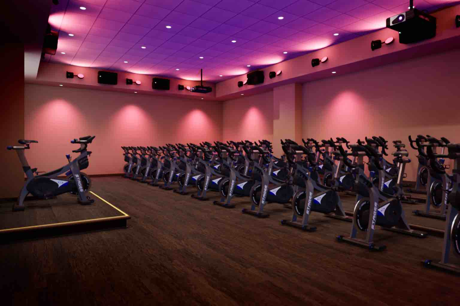 a dimly lit indoor cycle studio with stationary bikes