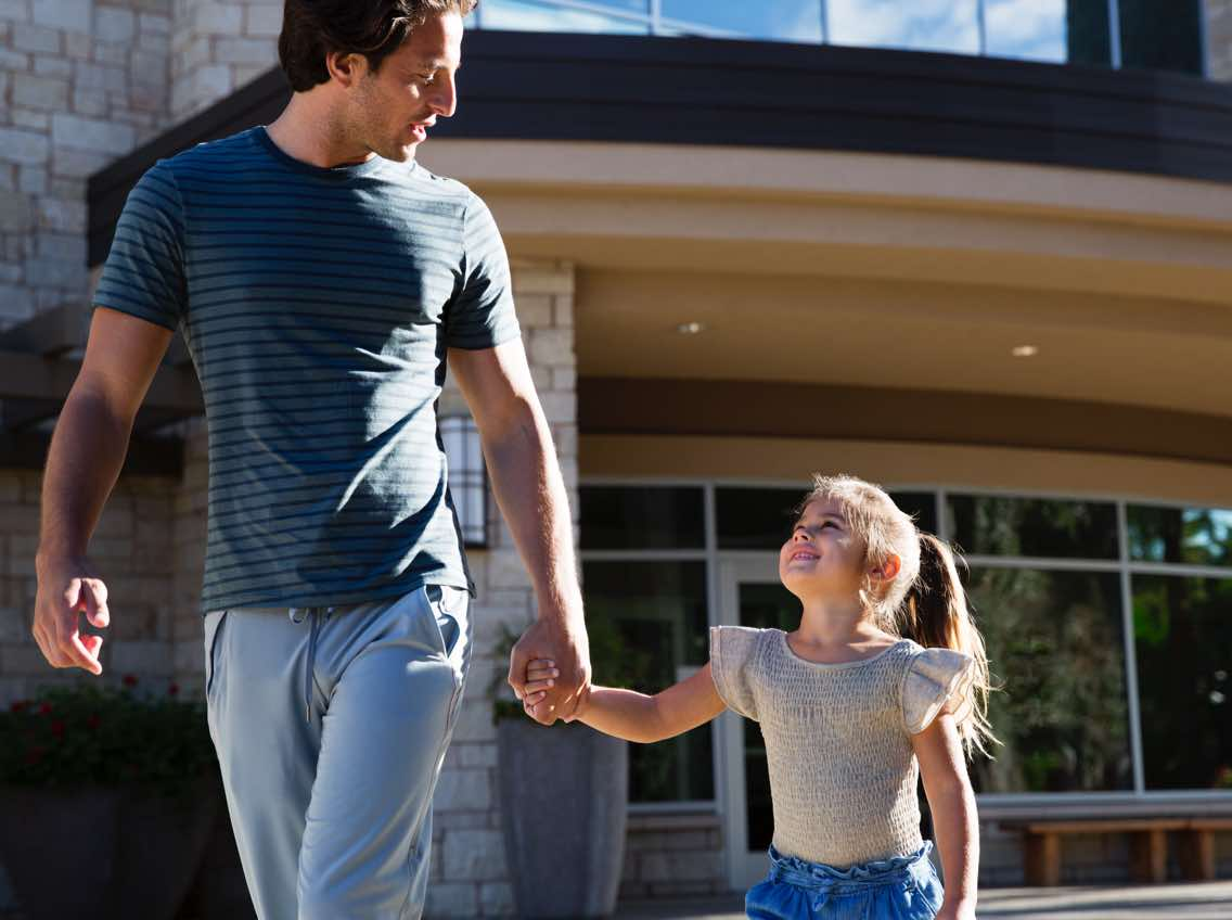 a young girl holds her dad's hand while exiting life time