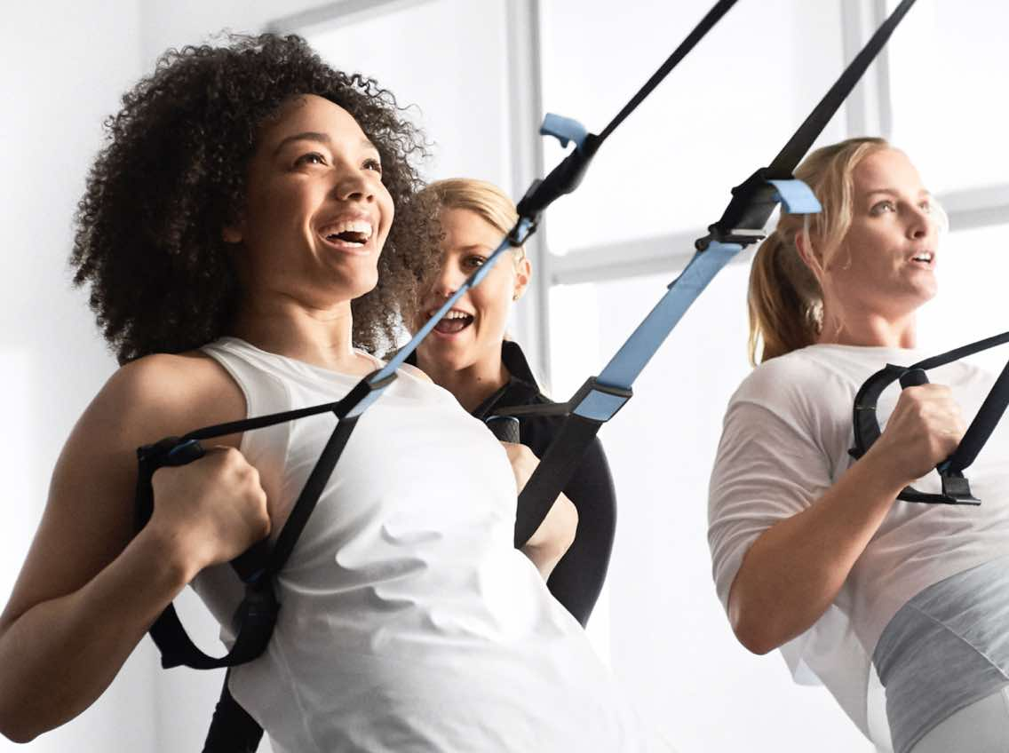 Smiling woman working out with a personal trainer at Life Time