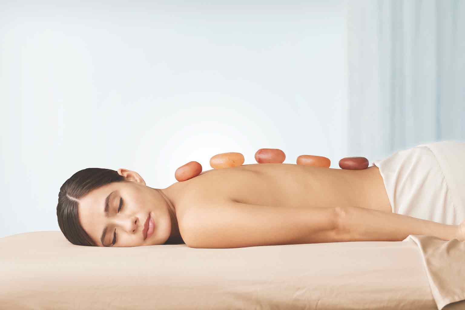 a woman laying down enjoying a warm stone spa treatment