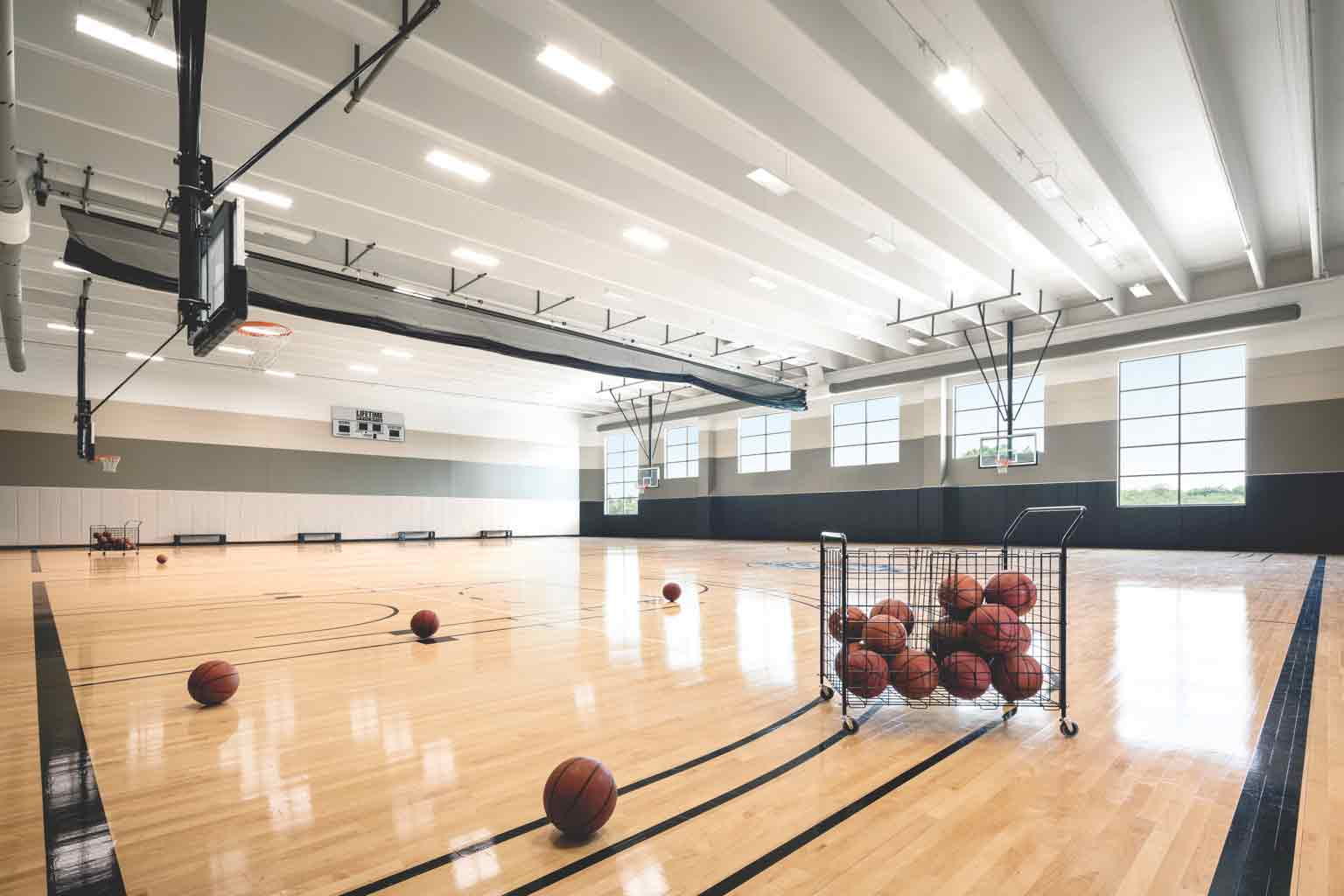 Life Time's spacious gym, featuring multiple hoops and basketballs