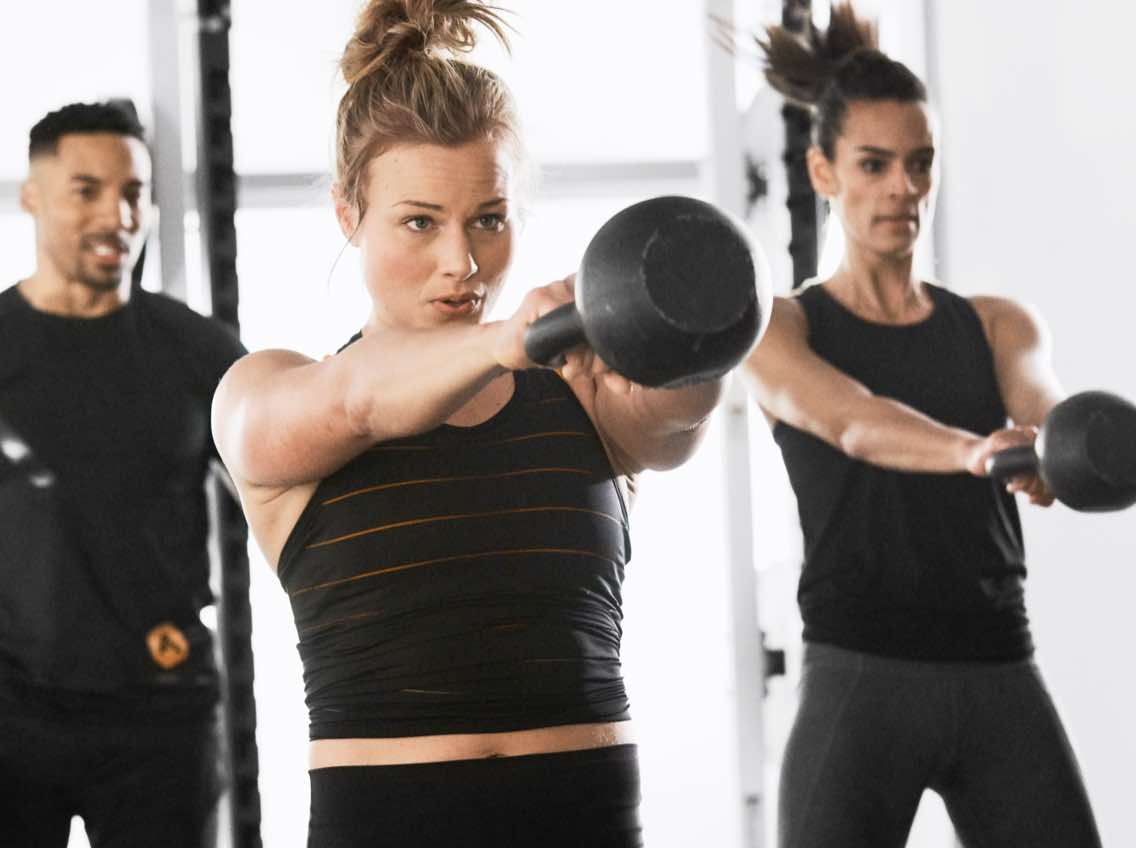 Woman swings kettlebell during an Alpha Class at Life Time