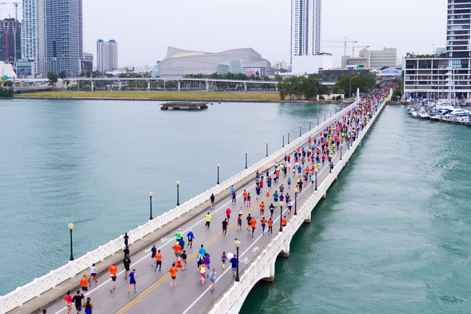 : A crowd of runners running across a bridge over water with city buildings in the background