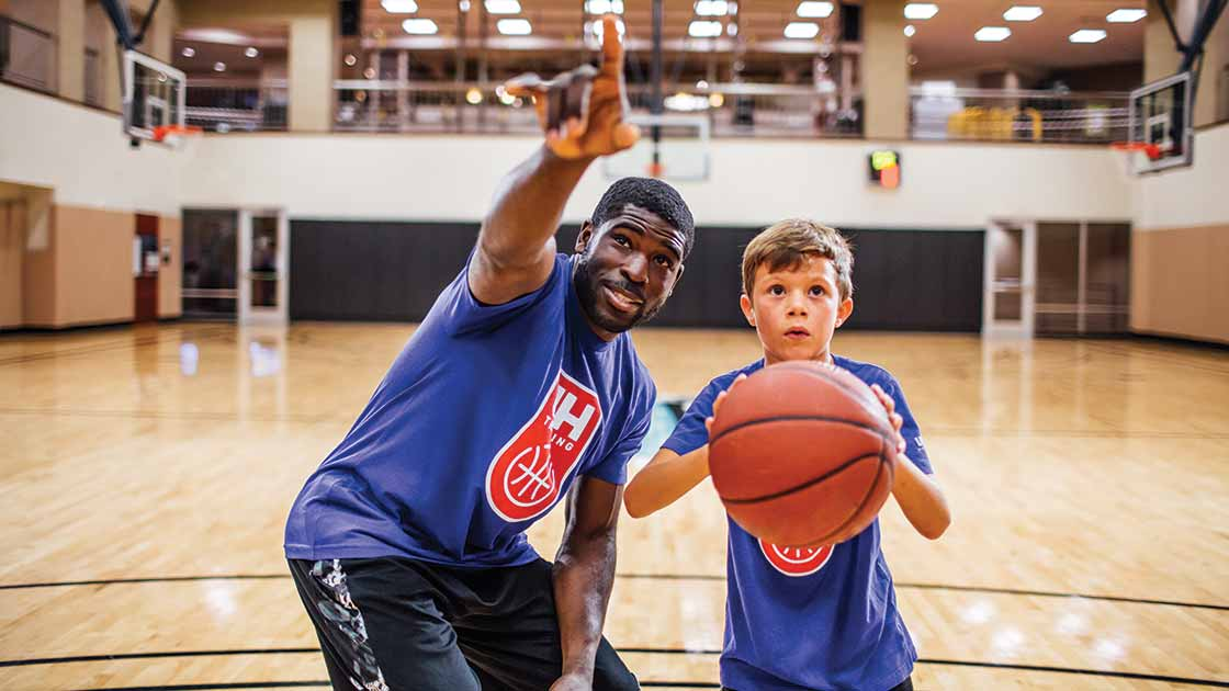 Image of a basketball coach teaching a boy to shoot a basket
