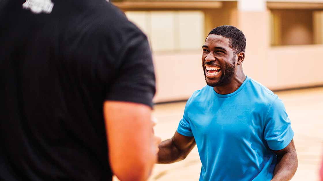 Smiling athletic man talking to another man on a basketball court