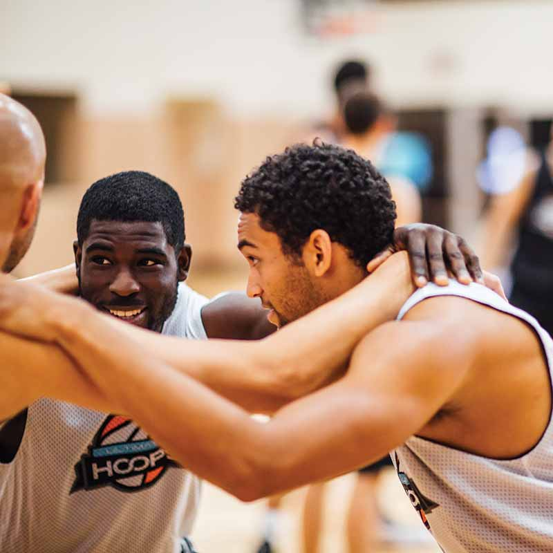 Three athletic men huddling on a basketball court