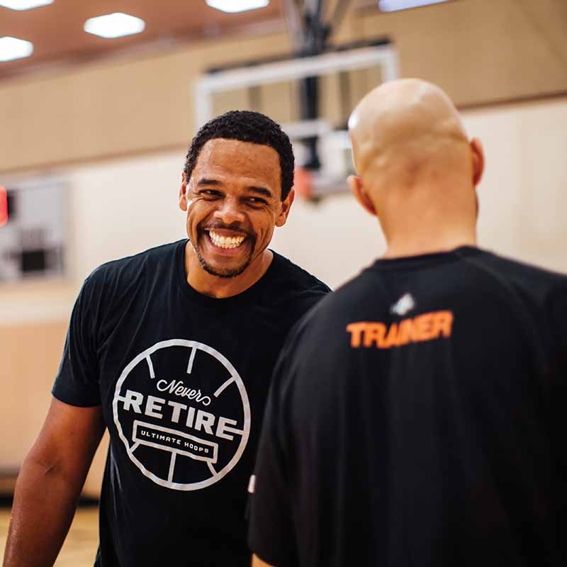 Two men laughing on a basketball court