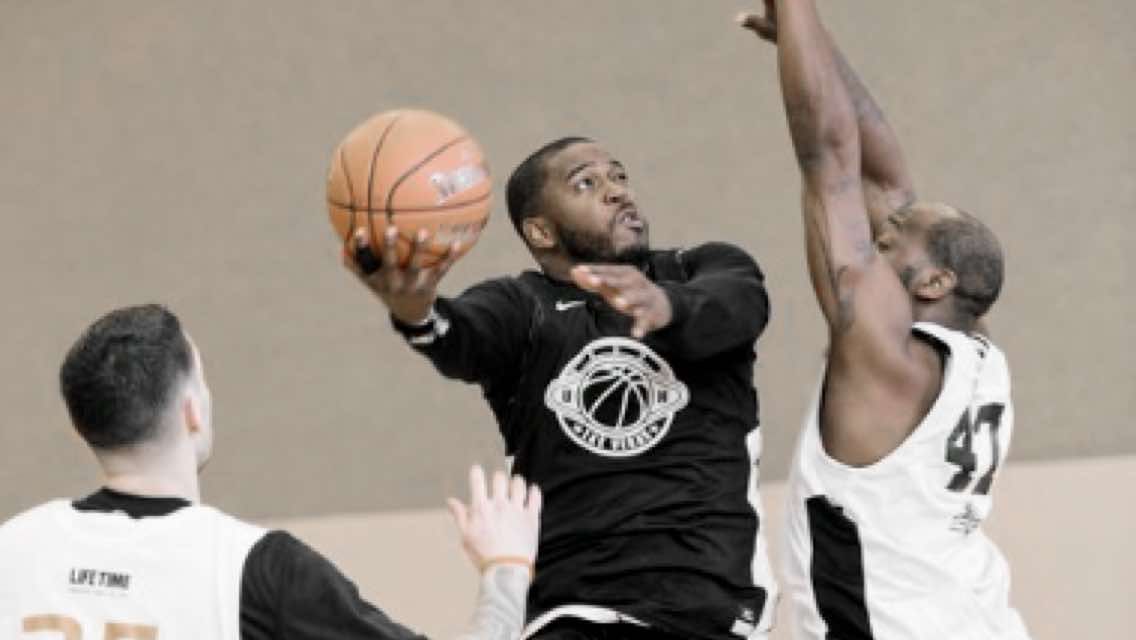 Man throwing a basketball up for a layup while another man plays defense