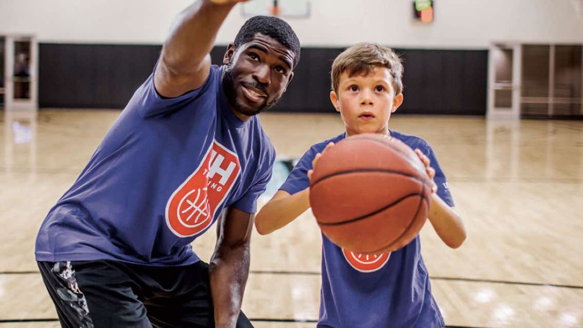 Man showing a male child how to shoot a basketball