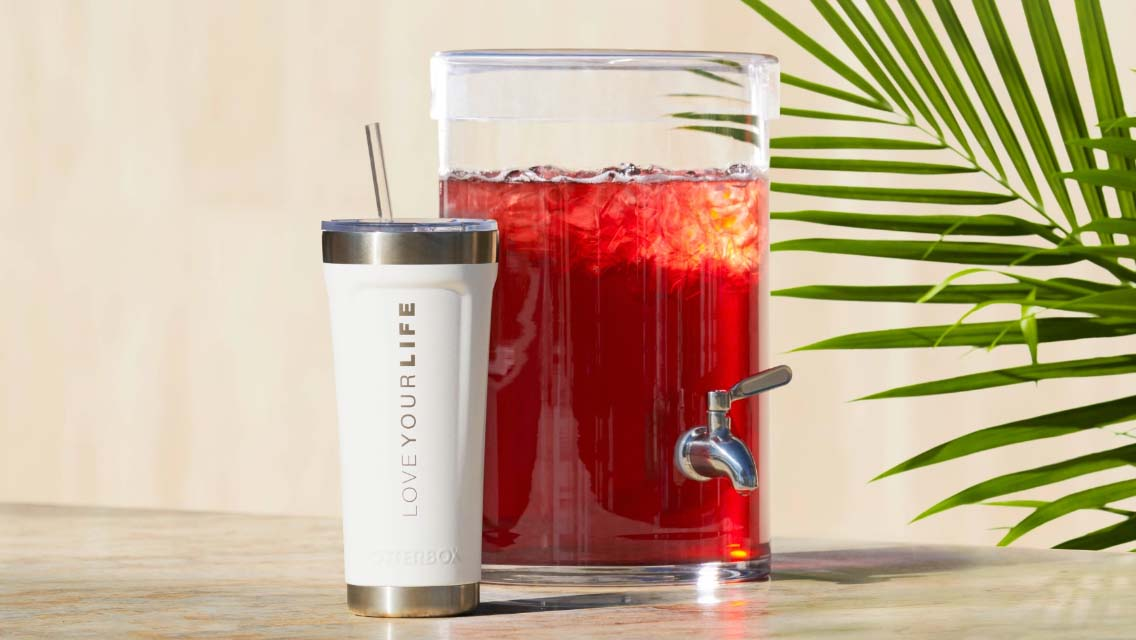 Life Time's new stainless steel Otterbox tea tumbler next to a pitcher of tea.