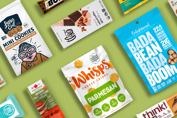 An assortment of healthy bars and snacks on a green background