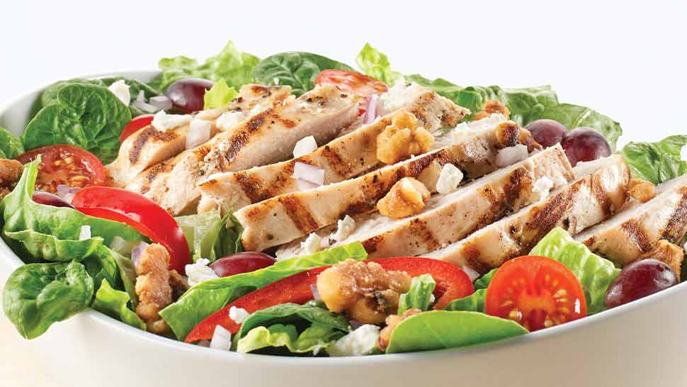 Mixed green salad with cherry tomatoes and grilled chicken in a bowl