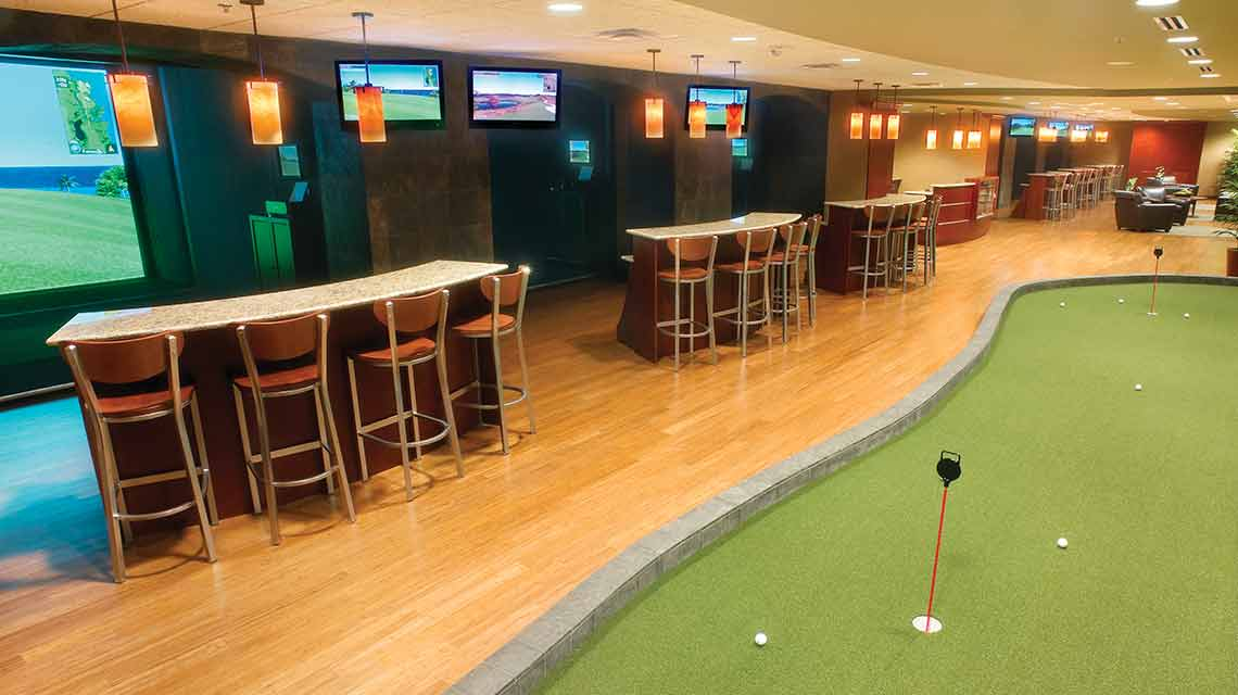 An indoor golf center featuring a putting green, a row of bar tables and bar seating and a ceiling lined with TV screens