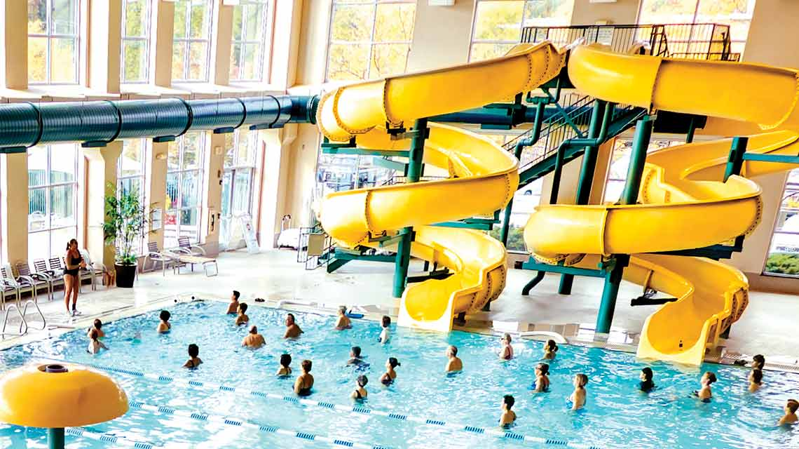 An aerial view of an expansive indoor pool with two curving yellow waterslides