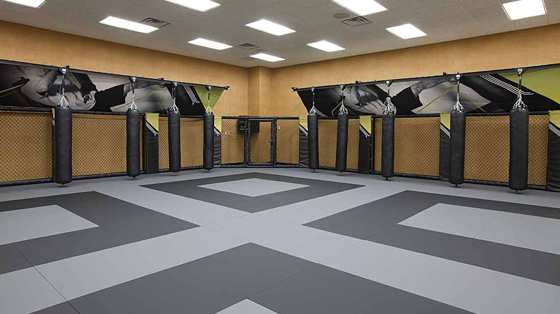 A well-lit mixed combat arts studio with a black and gray floor and walls lined with black hanging punching bags