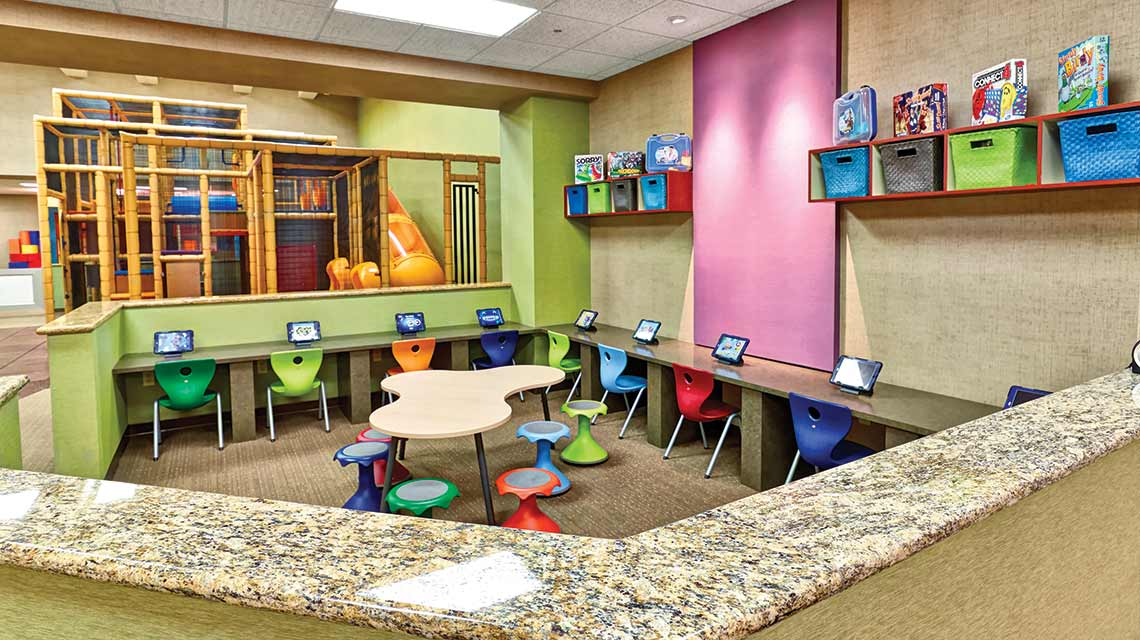 An aerial view of a children's media room with a row of tablets set on a low marble countertop with small, colorful children's chairs