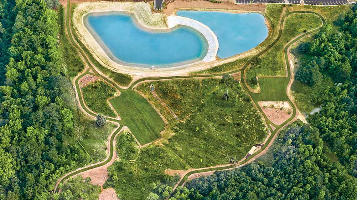 An aerial view of a crystal-clear blue outdoor pool surrounded by an outdoor fitness trail, grass and green trees