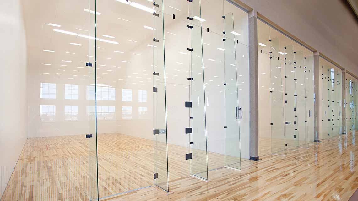A row of four empty racquetball courts with wooden floors and glass doors for entry
