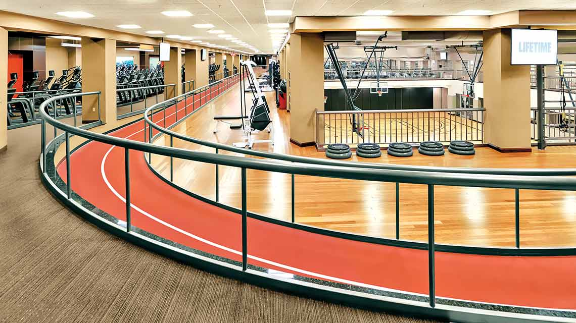 A wooden fitness floor circled by a red walking/running track with metal railings on both sides and cardio machines in the background