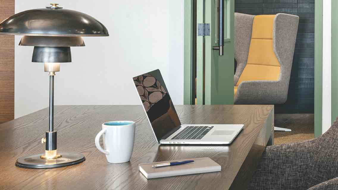 A modern workspace featuring a desk, laptop, desk lamp, coffee mug and cushioned swivel chair