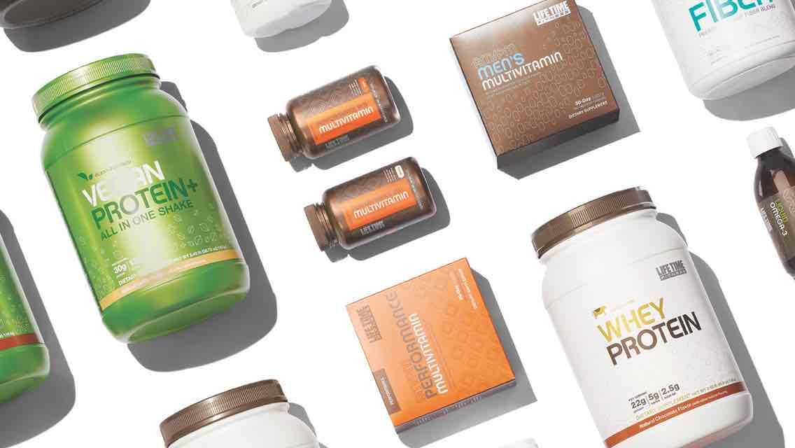 An array of Life Time supplements including containers of protein powder and bottles of multivitamins