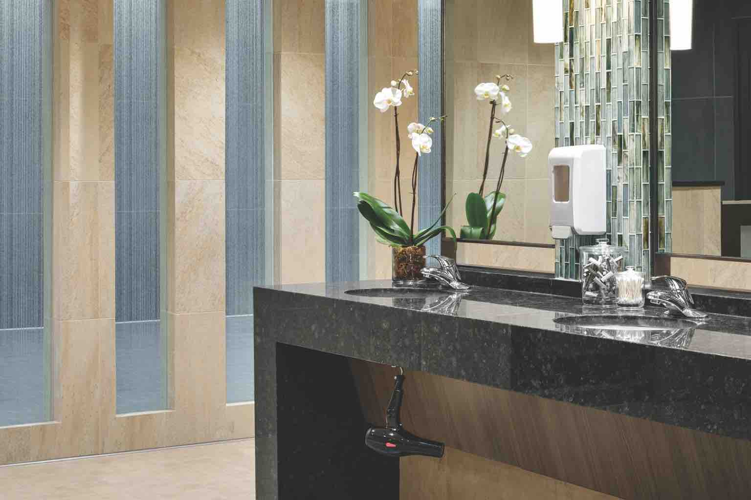 : A luxurious locker room with a row of three sinks in a black marble counter with tiled backsplash and hand soap dispensers